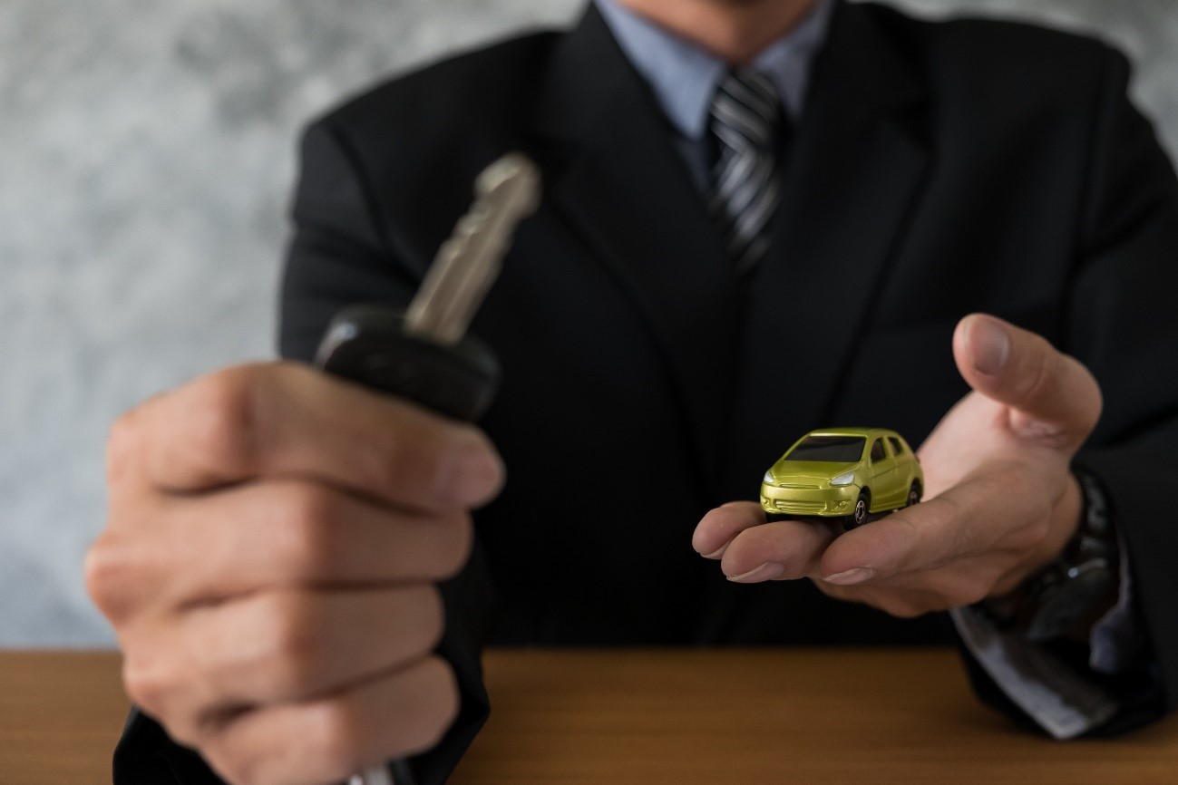 hombre sujetando unas llaves, con un coche en la mano